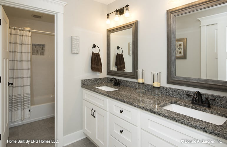 Bathroom with a dual sink vanity and a wet room equipped with a tub and shower combo.