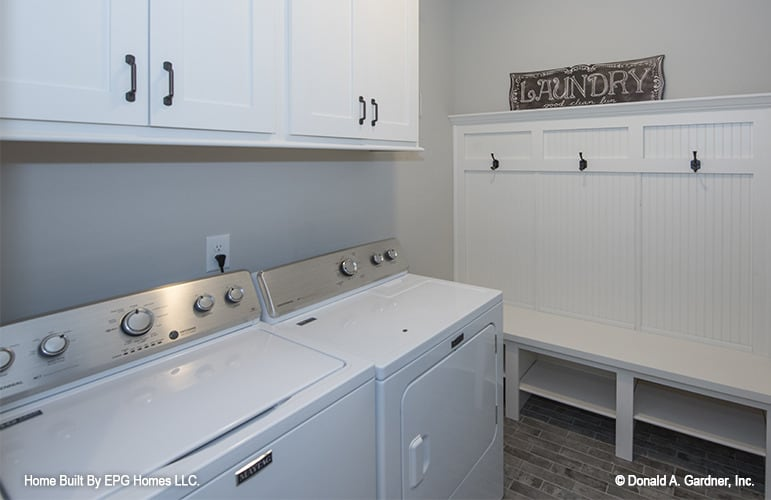 Utility room with top load washer and dryer, white overhead cabinets, and a built-in bench with coat hooks.