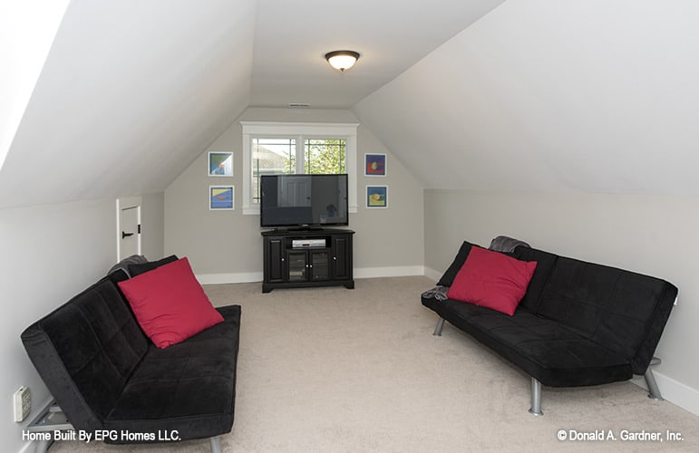 Bonus room with a TV and black velvet sofas under a coved ceiling.