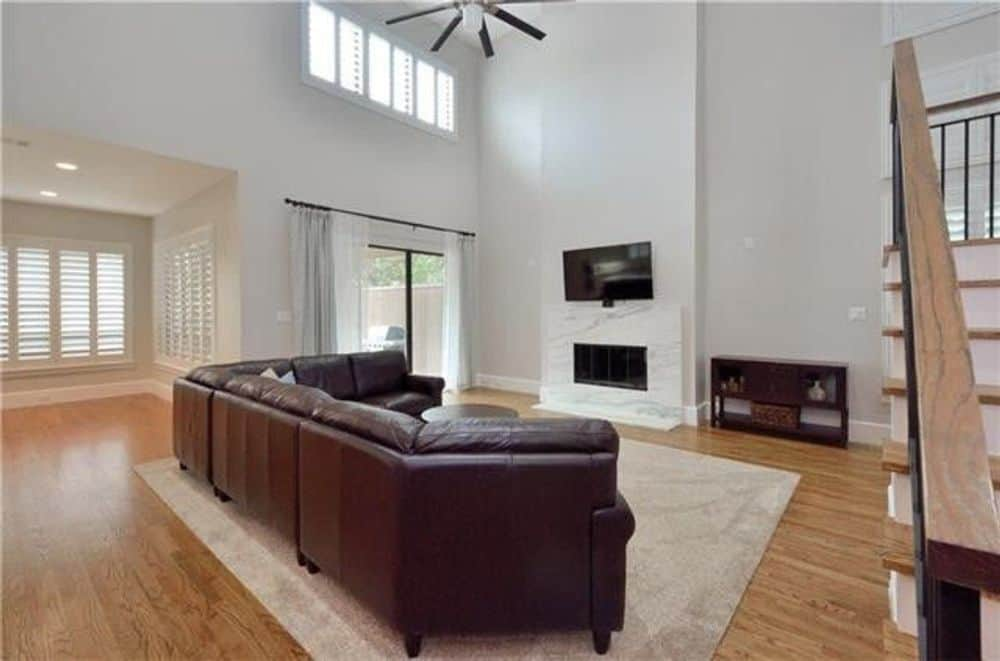 Family room with leather sectional and a marble fireplace topped with a TV.