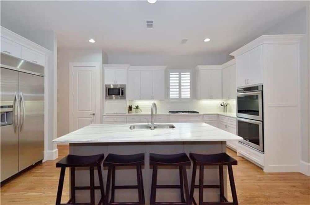 Kitchen with stainless steel appliances, white cabinetry, and a center island paired with wooden bar stools.