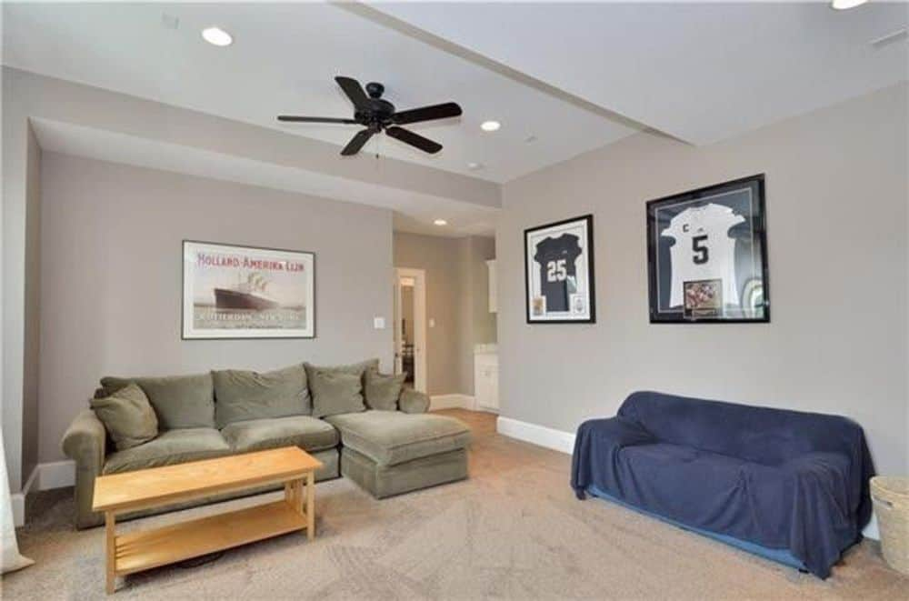 Recreation room with cozy sofas, a wooden coffee table, and framed wall arts adorning the gray walls.