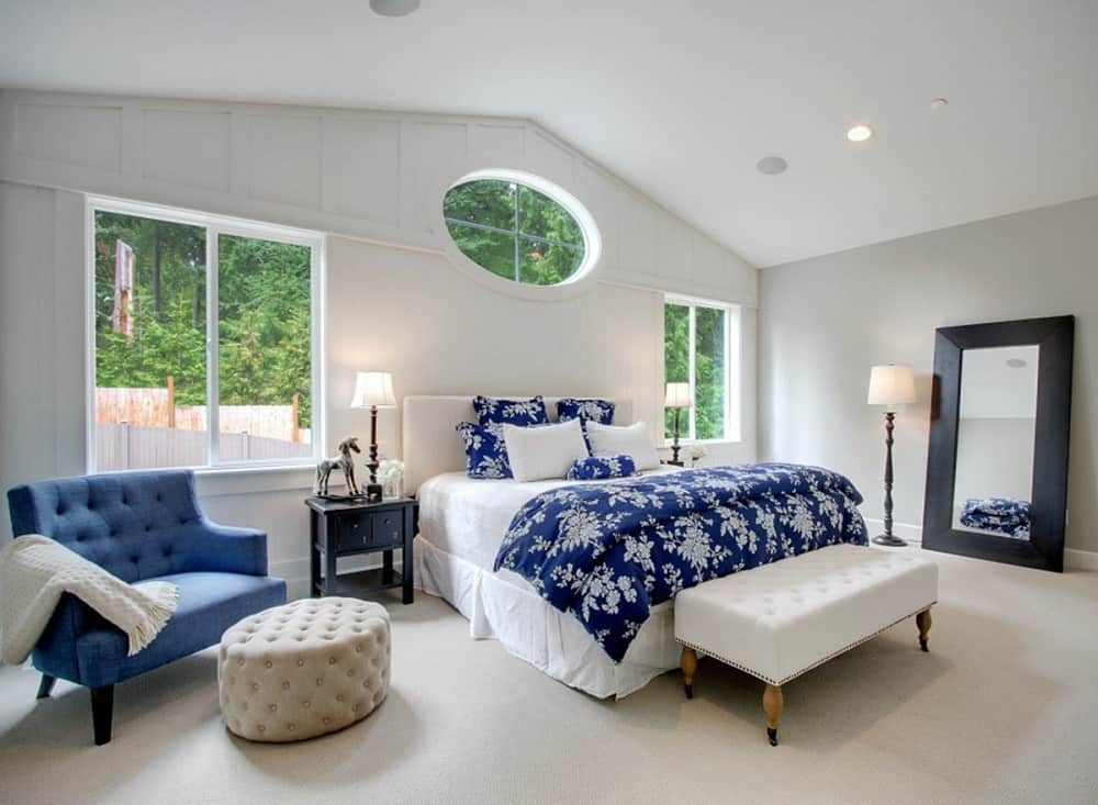 The primary bedroom has a white skirted bed, comfy tufted seats, and a full-length mirror. These are then complemented by the white walls, multiple windows, arched white ceiling and beige carpeting of the floor.