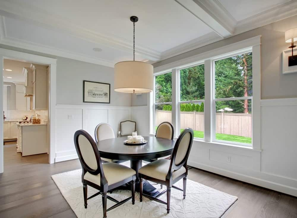 The dark wooden round dining table and matching cushioned oval back chairs stand out against the white wainscoting and white area rug on the hardwood flooring brightened by the natural lights coming in from the large windows.