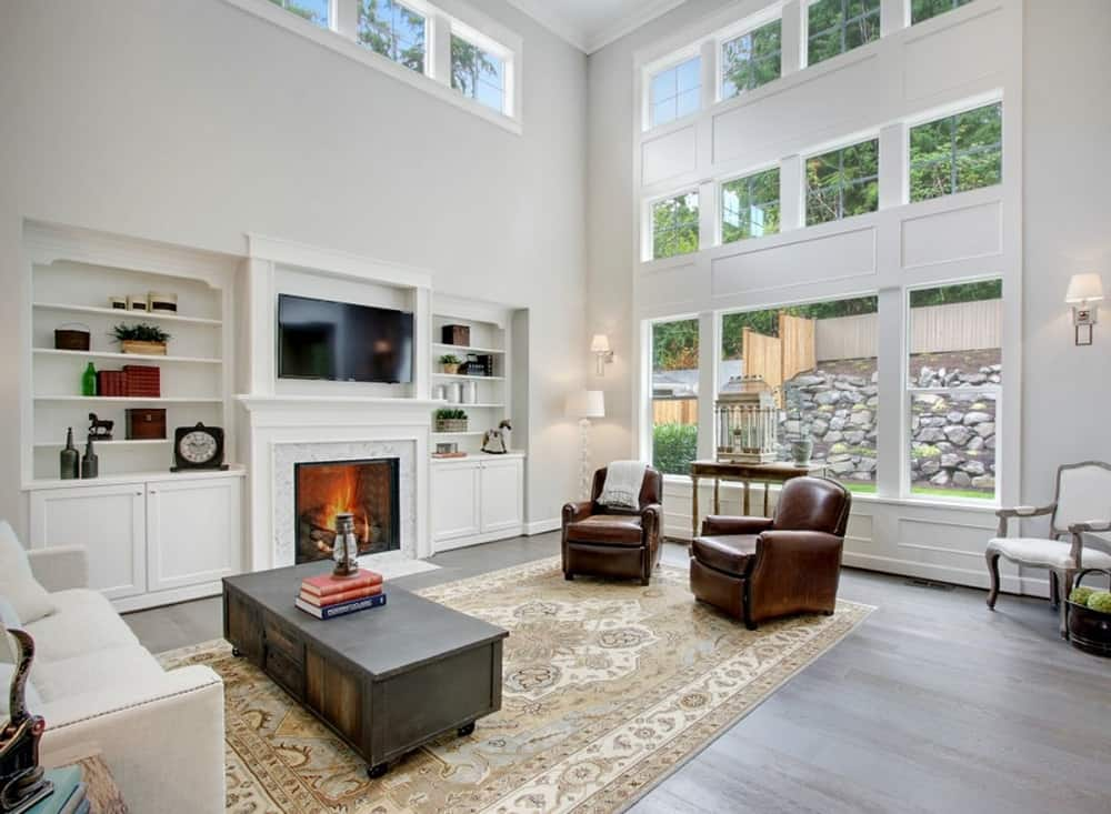 This is a bright living room with white walls and white built-in cabinets and shelves that are brightened by the natural lights coming in from the windows. These bright elements make the wooden coffee table and leather armchairs stand out.