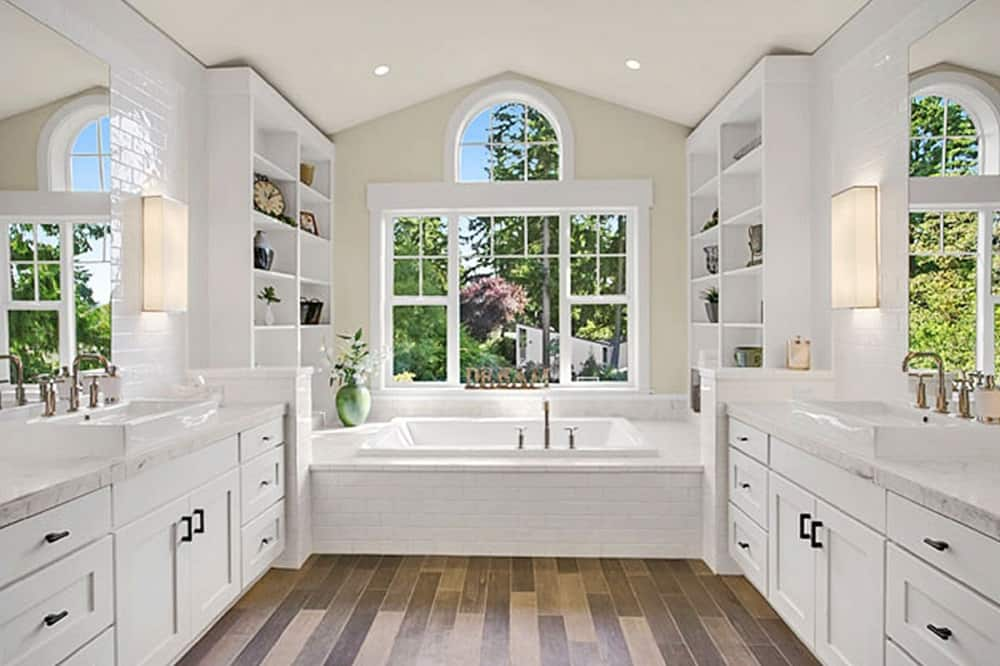 The primary bathroom has pure white cabinets and drawers on the vanities placed on opposite walls of the bathroom. On the far side is the large bathtub under the windows flanked by built-in open shelves on both sides.