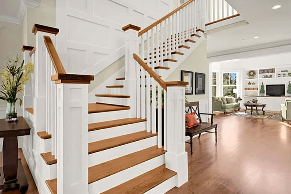 This is a close look at the foyer that has a large wooden staircase that has wooden steps that match the hardwood flooring. On the side of this is a brown bench with a throw pillow and wall artworks.