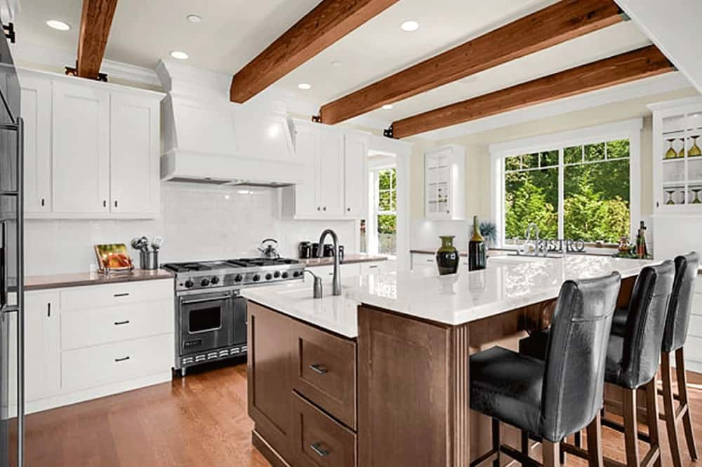 This is a close look at the kitchen with a large two-tiered kitchen island. This has a white countertop that is contrasted by the brown wooden cabinetry that matches the hardwood flooring and the exposed beams of the ceiling.
