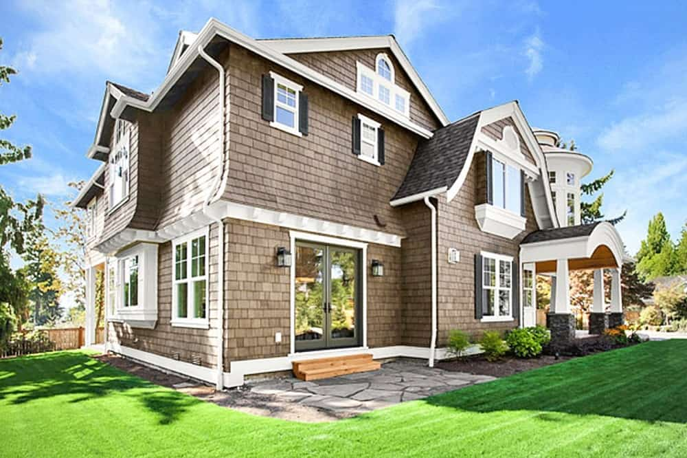 This is a view of the back of the house that has brown exterior walls with white accents. These are complemented by the lush landscaping of grass lawns, shrubs and a mosaic stone walkway and patio.