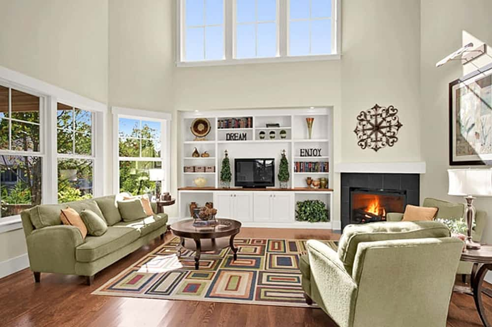 The spacious and bright living room has tall beige walls brightened by the large transom windows above the built-in entertainment cabinet beside the fireplace across from the green sofa set paired with a round coffee table on a patterned area rug.