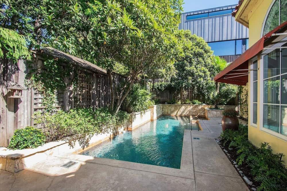 Rear lanai with a swimming pool bordered by a wooden fence and trees.