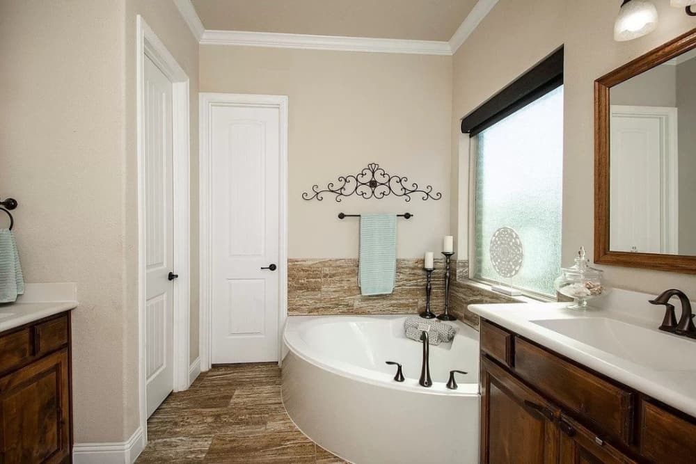Primary bathroom with double vanities and a deep soaking tub fixed under the picture window.