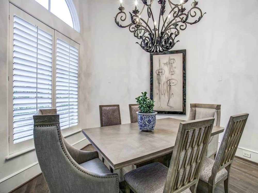 The formal dining room offers a wooden dining set well-lit by an ornate wrought iron chandelier.
