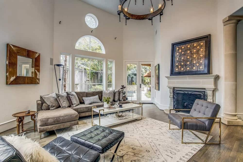 Family room with an L-shaped sectional, leather tufted chairs, and a fireplace.