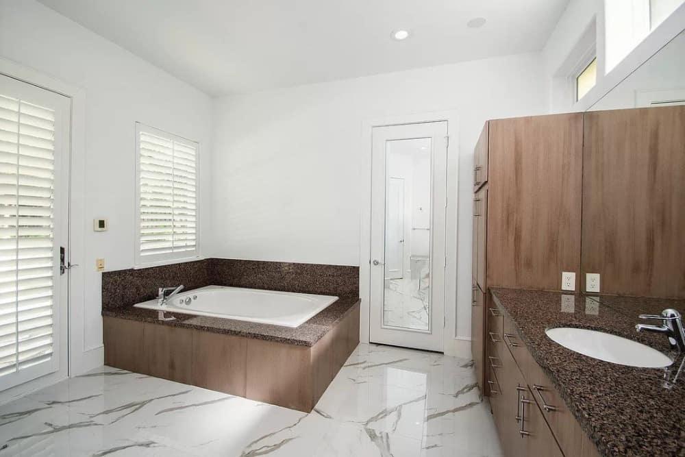 Bathroom with a sink vanity, a linen closet, and a drop-in bathtub over marble tile flooring.