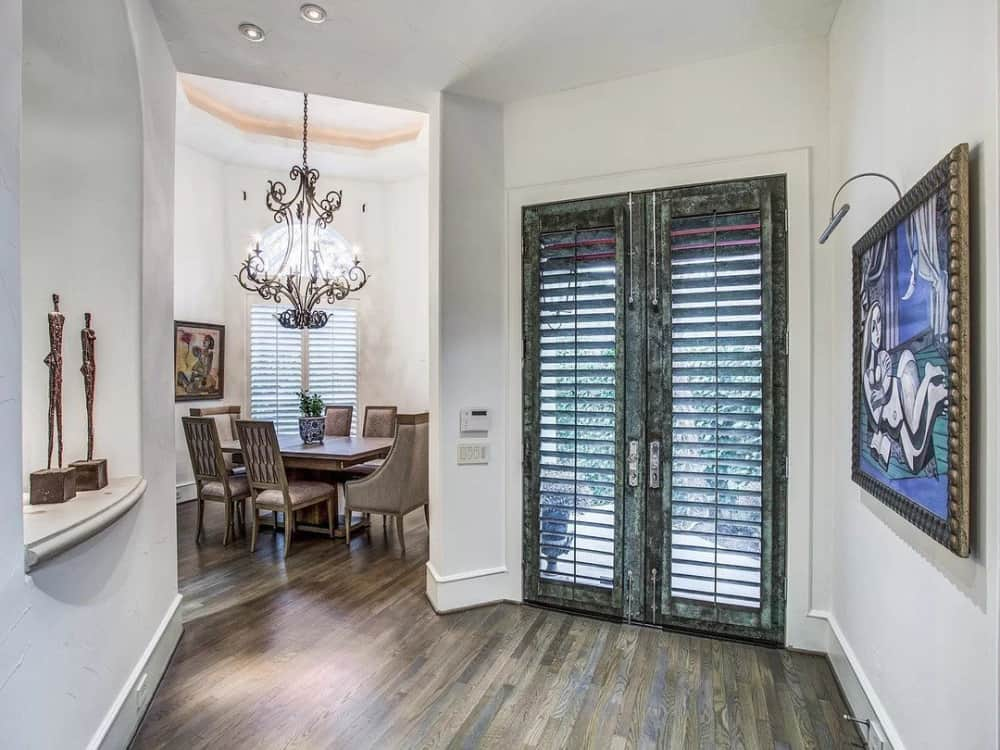Foyer with a louvered french door and a niche wall filled with decors.