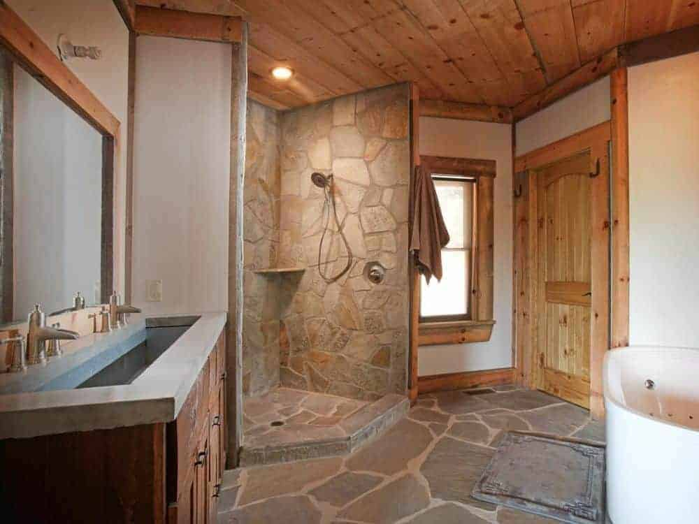 The bathroom has a mosaic stone flooring that extends to the walls of the shower area across from the bathtub beside the wooden vanity.