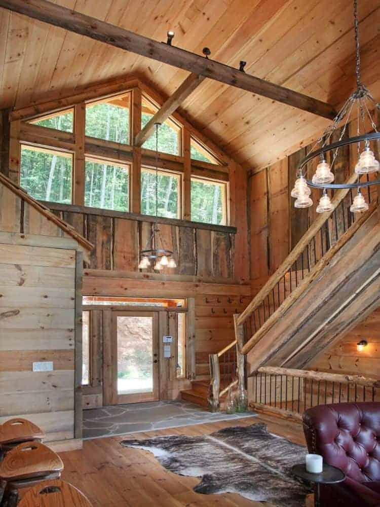 The foyer has tall wooden walls with a large set of transom windows above that brighten the wooden cathedral ceiling with exposed beams with a look at the staircase of the side.