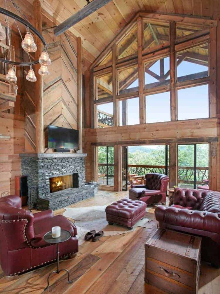 The large living room has a set of red leather sofas, armchairs and ottomans across from the stone fireplace. These are then complemented by the large glass wall on the far side.