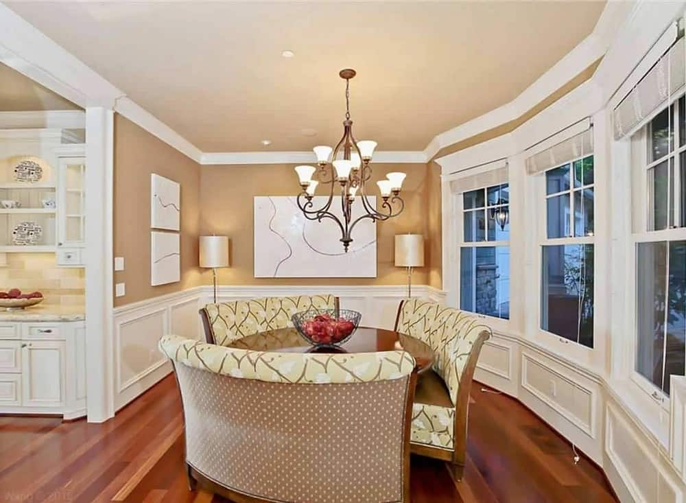 The dining room has a hardwood flooring that pairs well with the round wooden dining table surrounded by upholstered benches and topped with a wrought iron chandelier that has warm lighting and intricate details.