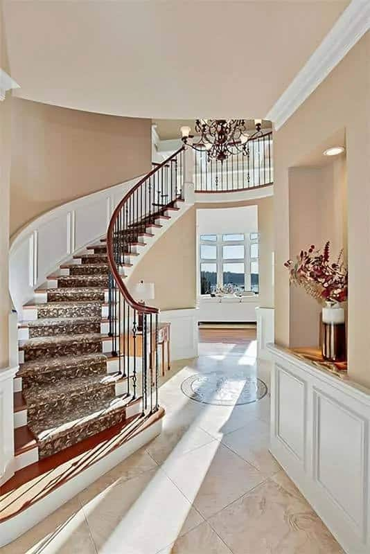 This is a close look at the foyer that has a tall ceiling, indoor balcony, a curved staircase with wrought-iron railings, wooden console table and a large chandelier in the middle.
