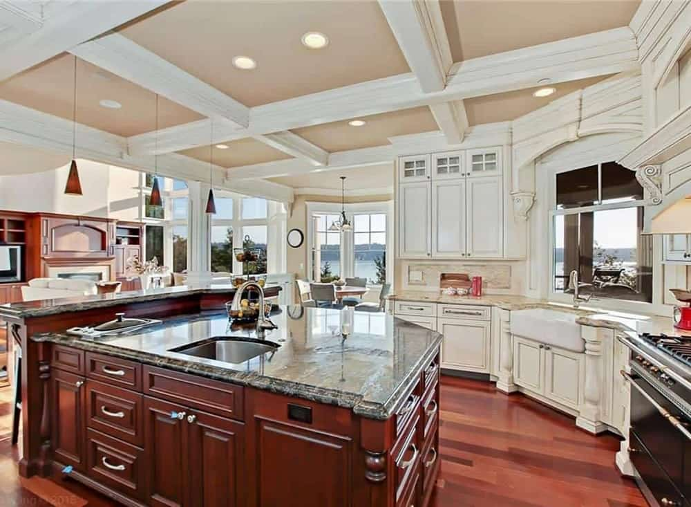 The kitchen has a large dark wooden kitchen island that has an attached breakfast bar. This matches the dark hardwood flooring and contrasts the bright beige cabinetry and coffered ceiling.