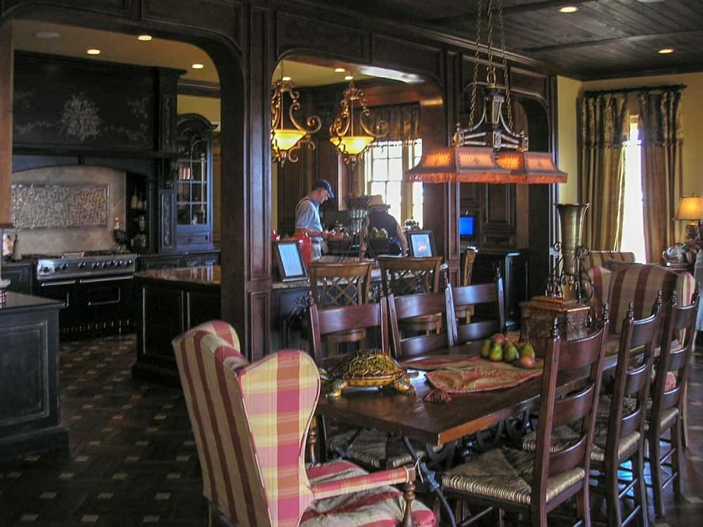 This is a close look at the formal dining room with a large wooden dining table surrounded by wooden chairs and a couple of cushioned chairs at the heads.