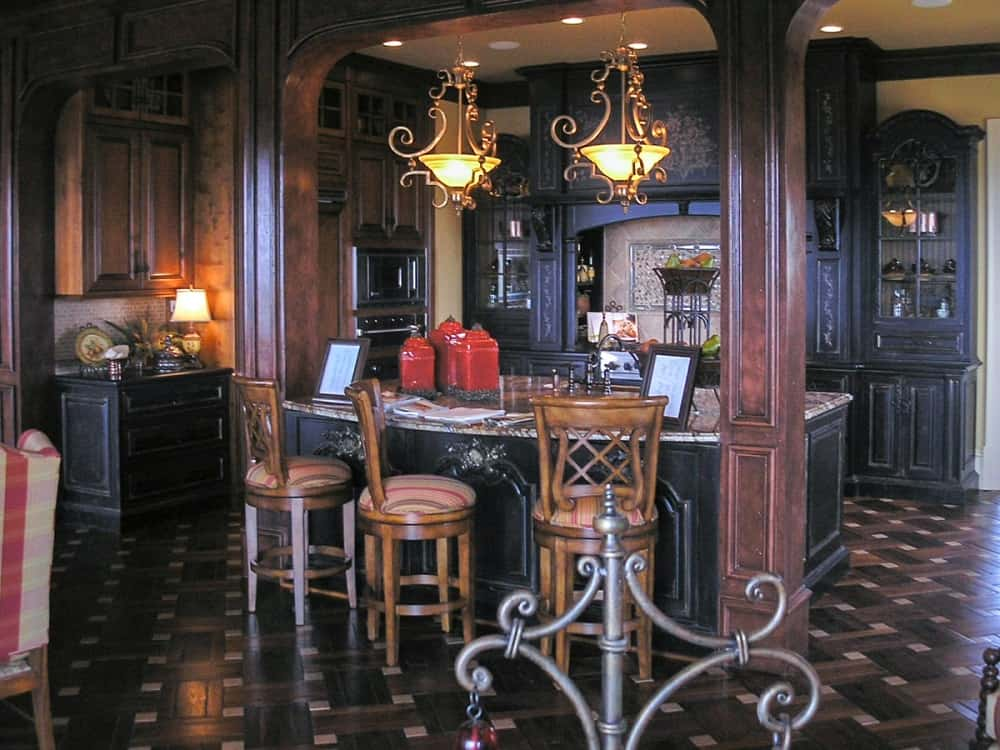 This is a close look at the kitchen that has dark cabinetry lining the walls matching with the patterned dark hardwood flooring. This also has a large kitchen island with a couple of large wooden pillars.
