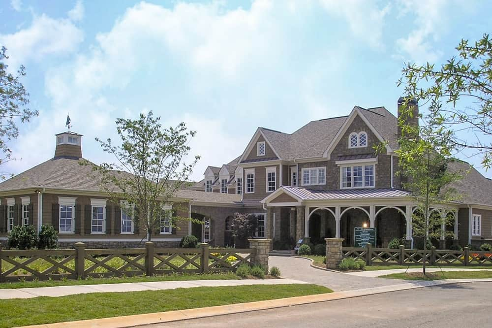 This is an exterior view at the front of the house that has brown exterior walls complemented by the landscaping that has grass lawns, flowering shrubs, tall trees and a concrete driveway.