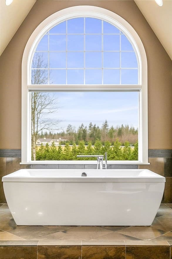 This is a close look at the primary bathroom that has a large white porcelain freestanding bathtub placed under the large arched window topped iwth a beige cathedral ceiling.