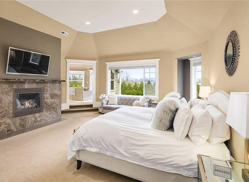 The primary bedroom has a large white bed surrounded by consistent beige walls, tray ceiling and beige carpeting. Across from this is the gray fireplace topped with a wall-mounted TV.