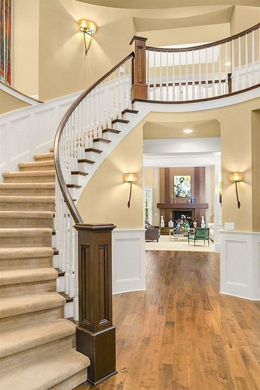 This is a close look at the foyer with a large curved staircase topped with a tall ceiling, tall beige walls and white wainscoting that contrast the hardwood flooring.
