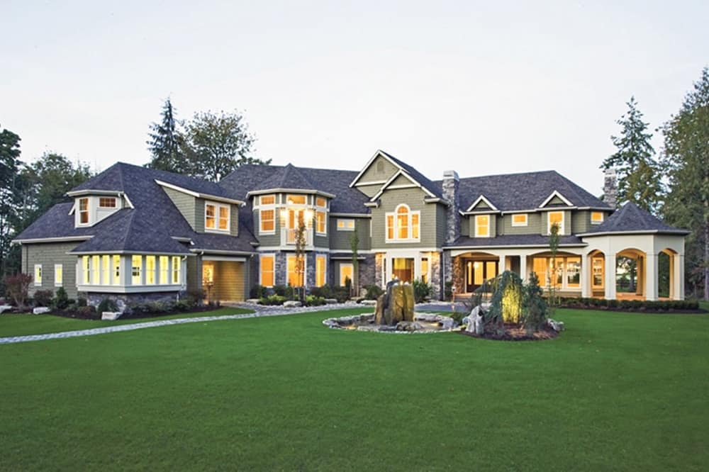 This is a view of the front of the shingle-style home that has a lush landscaping of large grass lawns, fountains, miniature gardens and shrubs that bring color to the exterior walls of the house.