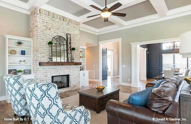 Great room with a coffered ceiling, a leather sofa, patterned armchairs, and a brick fireplace topped with an arched mirror.