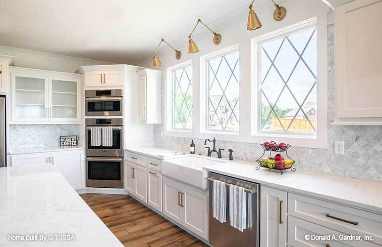 The kitchen includes stainless steel appliances, a farmhouse sink, and three-paneled windows.