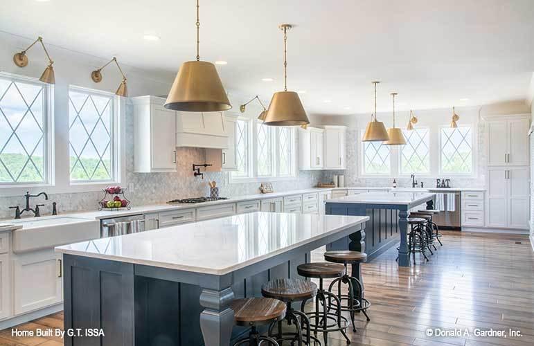 Kitchen with white cabinetry, two islands, and matching brass sconces and dome pendants.