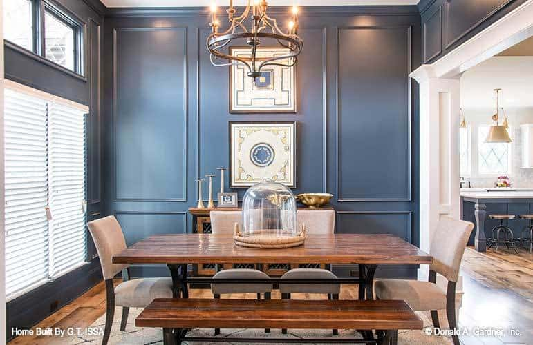 Formal dining room with blue wainscoted walls, a wooden buffet, and a rectangular dininng set well-lit by a wrought iron chandelier.