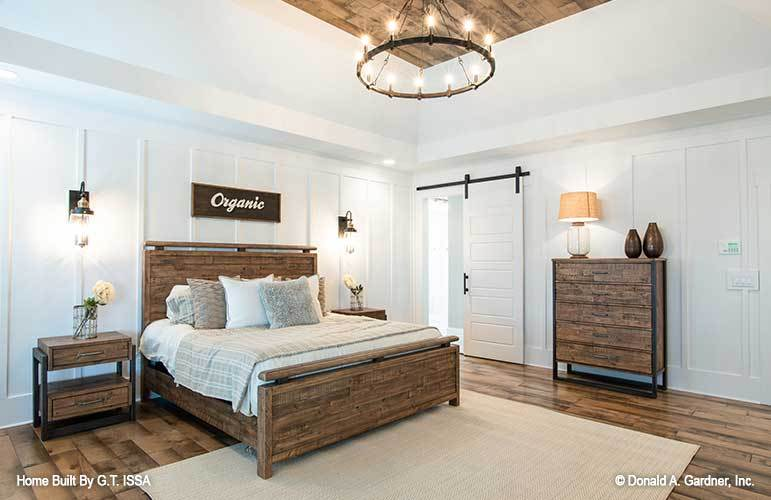 Primary bedroom with natural wood furnishings and a barn door that opens to the primary bath.