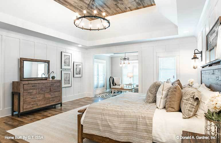 A stunning coved ceiling adorned with wood planks and round chandelier crowns the primary bedroom.
