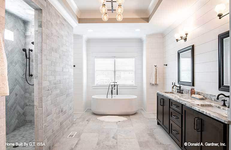 The primary bathroom offers a walk-in shower, a freestanding tub, and a dual sink vanity fitted with wrought iron fixtures.