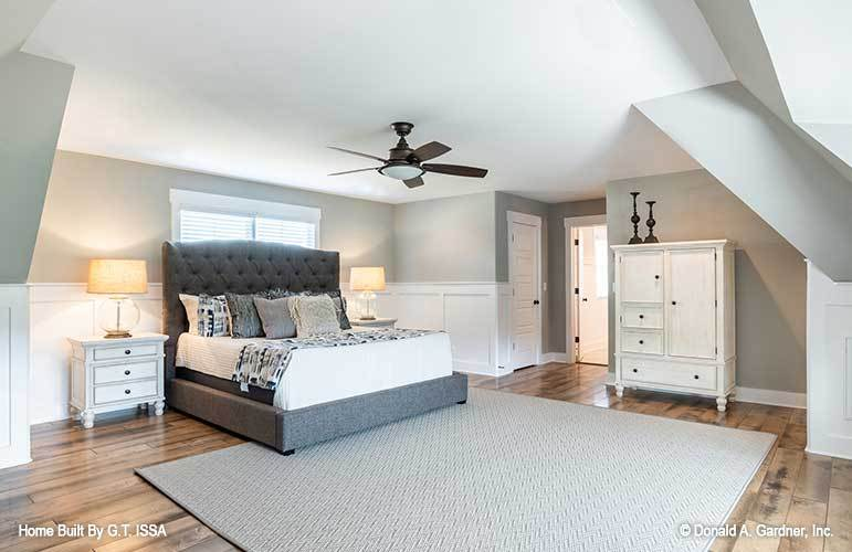 Bedroom with a tufted bed, white cabinets, and gray walls graced with white wainscoting.