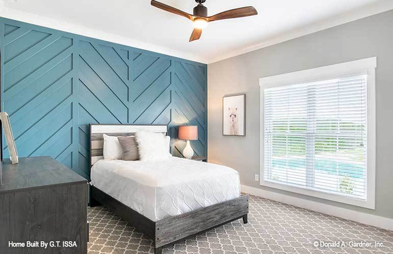 A blue chevron accent wall sets a nice backdrop to the dark wood bed of this bedroom.
