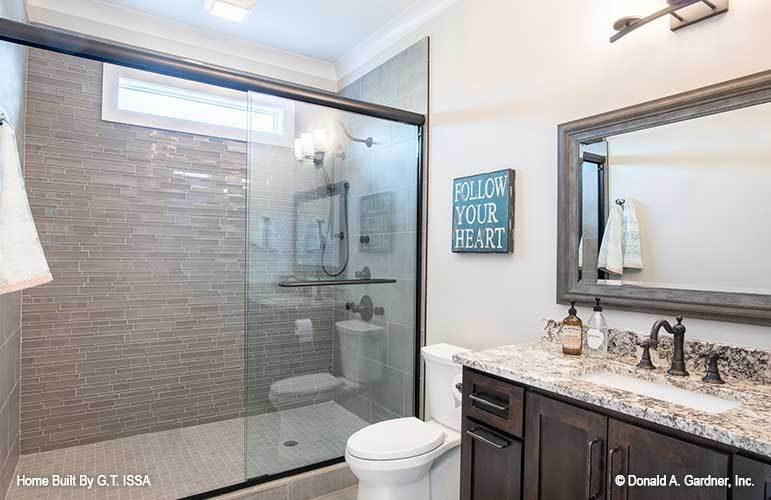 Another bathroom wtih a sink vanity, a toilet, a nd a walk-in shower accentuated with linear mosaic tile backsplash.