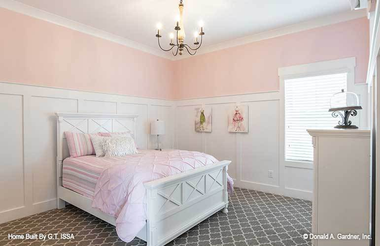 This bedroom features pink and white wainscoted walls, white furnishings, and gray patterned carpet flooring.