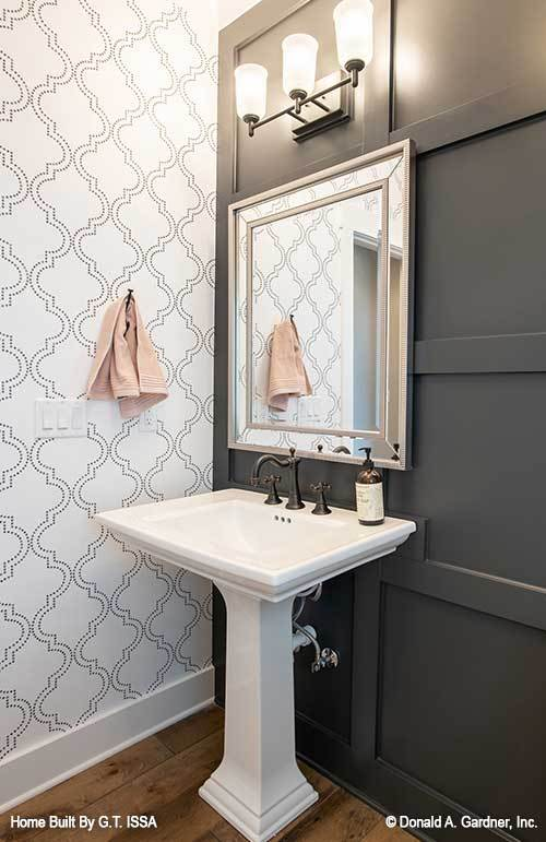 Powder room with a pedestal sink paired with a chrome framed mirror and glass sconces.