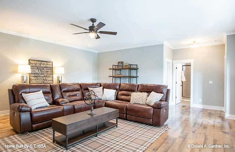 Recreation room with an L-shaped leather sectional and a wooden coffee table over a plaid area rug.