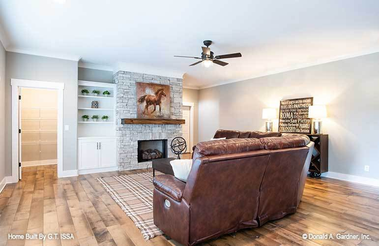 The recreation room includes a stone fireplace and white built-in cabinet.