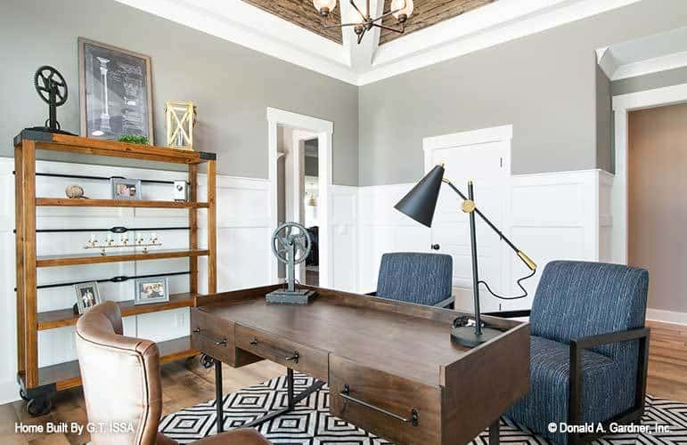 Study with a wooden shelving unit and a wooden desk complemented with upholstered chairs.