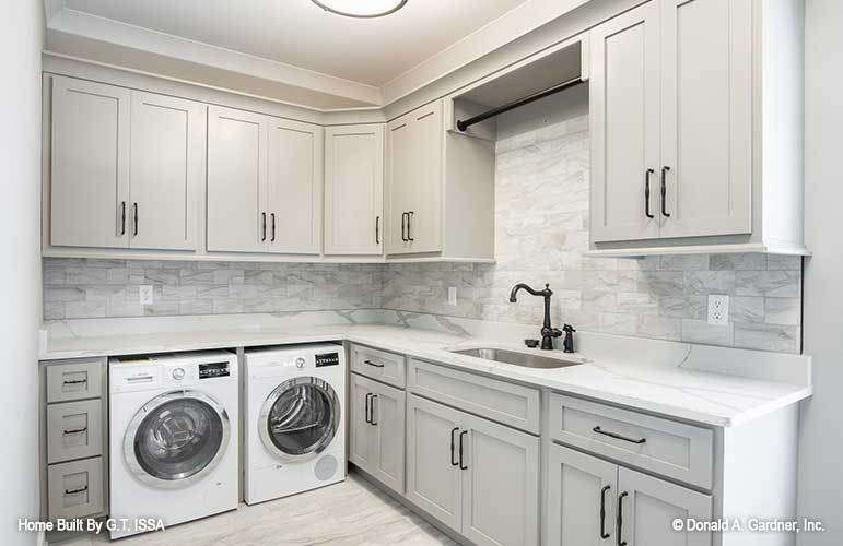 Laundry room with front-load washer and dryer, white cabinets, marble countertops, and a utility sink.
