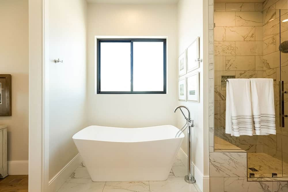 This is a close look at the primary bathroom that has a glass enclosed shower area with white marble tiles beside the alcove of the freestanding bathtub under the window.